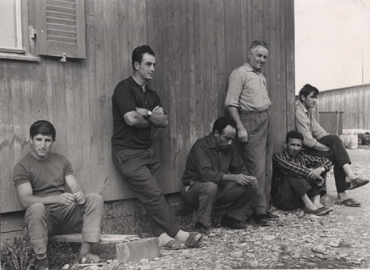 Emigranti italiani davanti a una baracca della centrale elettrica di Aarberg in Svizzera, 1965
