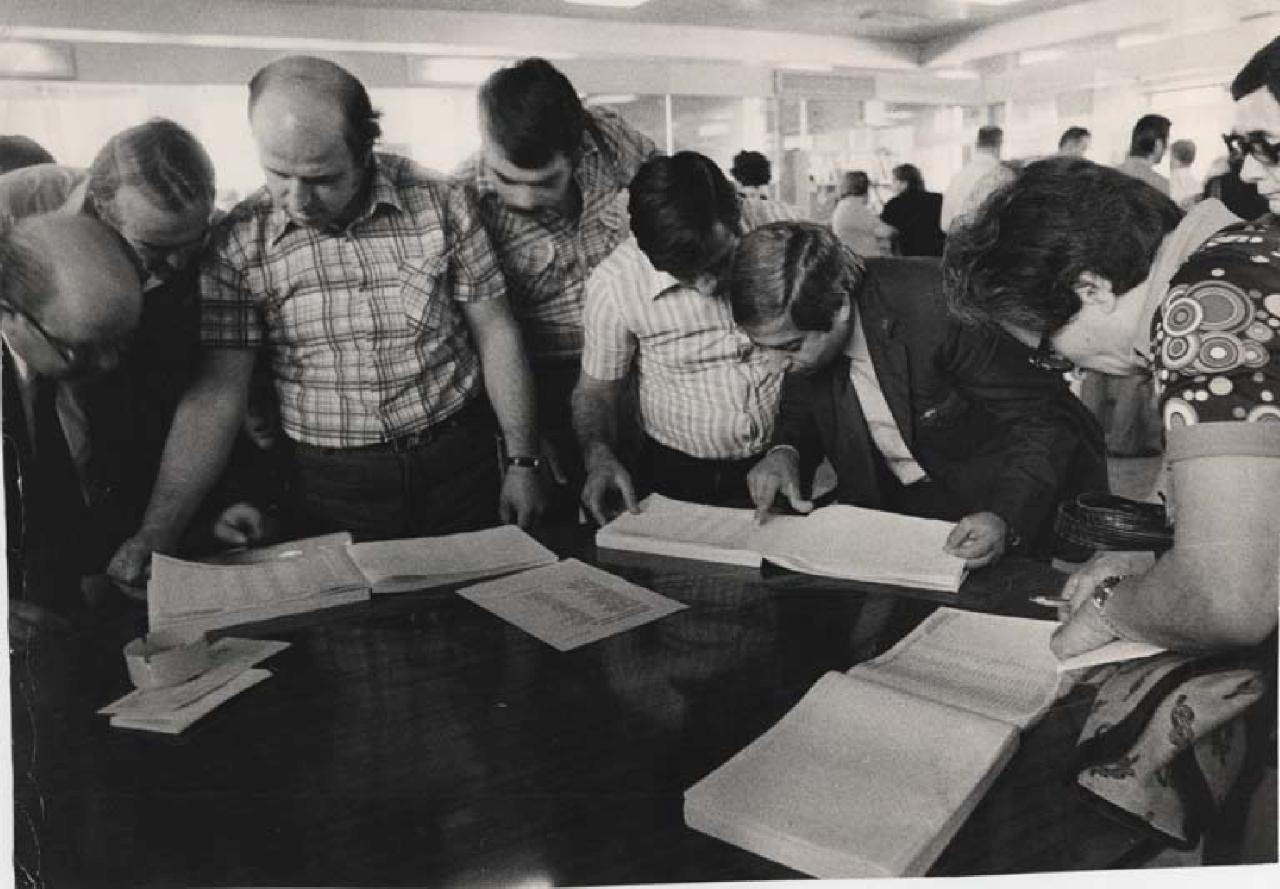 Alcune persone consultano le liste con le graduatorie per l'assegnazione delle case popolari, all'interno degli uffici Iacp, 1977
